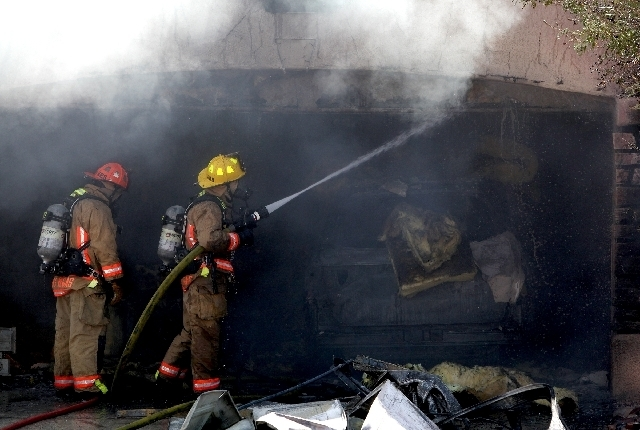 Las Vegas firefighters extinguish a fire that started in the garage of a home at 2312 Sun Cliffs St. on Wednesday morning. One person was treated with oxygen at the scene. (Justin Yurkanin/Las Veg ...