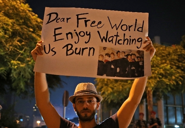 A Syrian man who lives in Beirut, holds up a placard during a vigil against the alleged chemical weapons attack on the suburbs of  Damascus, in front the United Nations headquarters in Beirut, Leb ...