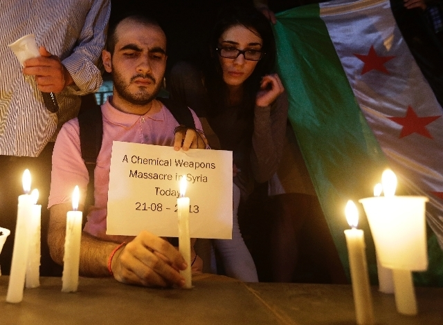 A Syrian man who lives in Beirut, lights a candle and holds a placard during a vigil against the alleged chemical weapons attack on the suburbs of  Damascus, in front the United Nations headquarte ...