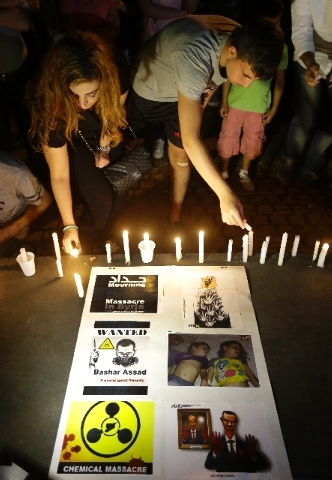 Lebanese citizens, light candles during a vigil against the alleged chemical weapons attack on the suburbs of Damascus, in front the United Nations headquarters in Beirut, Lebanon, Wednesday. (AP  ...