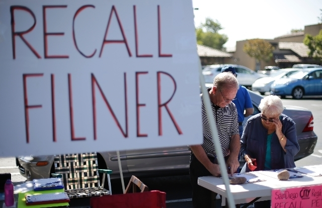 Greg Timms, left, signs a petition to recall San Diego Mayor Bob Filner, alongside Tana Piontek, right, at a stand set up in the parking lot of a shopping center
