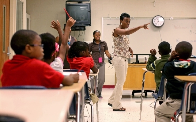 Ronald E. McNair Discovery Learning Academy first-grade teacher Sherlita Bickham directs her class on Wednesday, a day after an armed suspect cause an ordeal at their school in Decatur, Ga. (Jason ...