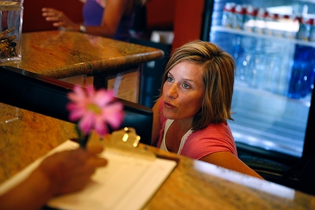 Stephanie Dixon, executive director of Summerlin Yoga, works at the front desk at the yoga studio in Las Vegas on Aug. 20.