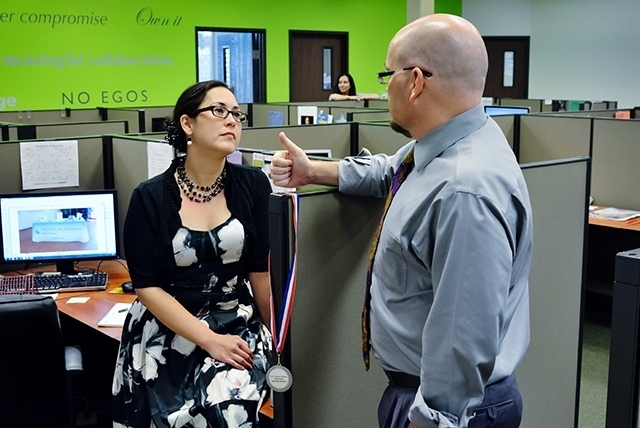 Aimee Riley, a grass-roots specialist at MassMedia, talks with James Stover, an account manager with the firm, at the firm's offices Aug. 16 in Henderson.