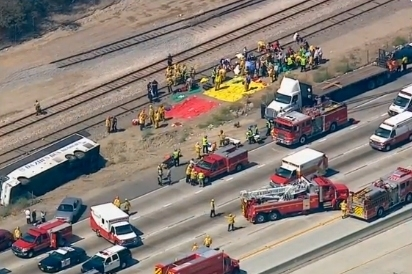 This video image provided by KABC-TV shows rescue officials working the scene of an accident where a tour bus, left, crashed  and turned over injuring multiple passengers.