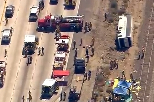 This video image provided by KABC-TV shows rescue officials working the scene of an accident where a tour bus, left, crashed  and turned over injuring multiple passengers on Thursday.