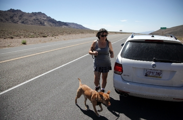 Brenda Priddy takes a break to walk her dog, Hunter, at Towne Pass in Death Valley. Hunter, whose full name is Hunter S. ThompsonJr., rides along as she stalks test cars. She found him injured a ...