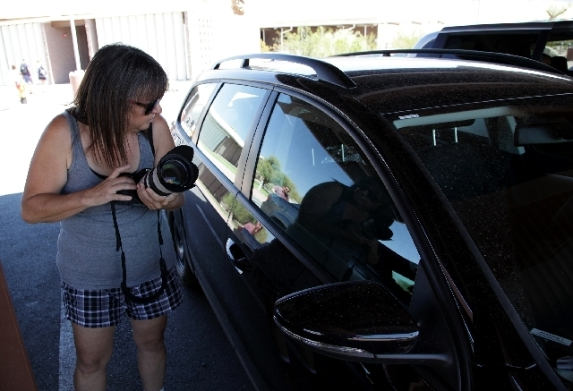 Brenda Priddy checks out a Volkswagen prototype parked Monday in front of the Death Valley visitor center in Furnace Creek. She has photographed thousands of automobiles in development over the pa ...