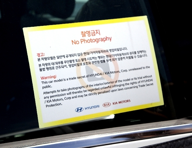 A sign on a test car parked Monday at Furnace Creek Ranch tries to warn off photographers, but car spy Brenda Priddy says it's an empty threat. Automakers have tested vehicles in Death Valley's  ...