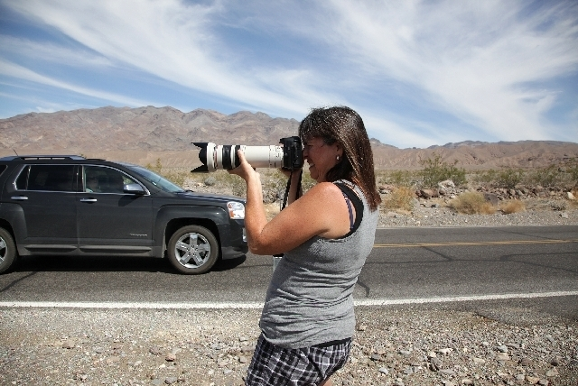 Brenda Priddy aims her camera at a prototype car being tested in Death Valley National Park. An automotive spy photographer since the early 1990s,  her photos are a hot commodity for car magazines ...