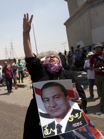 A supporter of Egypt's deposed autocrat Hosni Mubarak holds a poster of him and chants slogans in front of Tora prison.