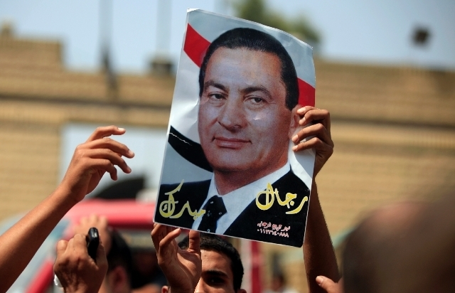 A supporter of Egypt's deposed autocrat Hosni Mubarak holds a poster of him and chants slogans in front of Tora prison, where Mubarak has been held, in Cairo.