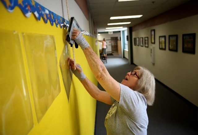 Full-day Kindergarten instructional assistant Ruby Crabtree prepares the hallways before the start of the school year at Robert L. Forbuss Elementary School in Las Vegas on Thursday.