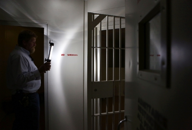 Mark Larson, assistant manager of facilities for Real Property Management, holds a light Thursday near a holding cell at Clark County's old courthouse, located at 200 S. Third St. The courthouse, ...