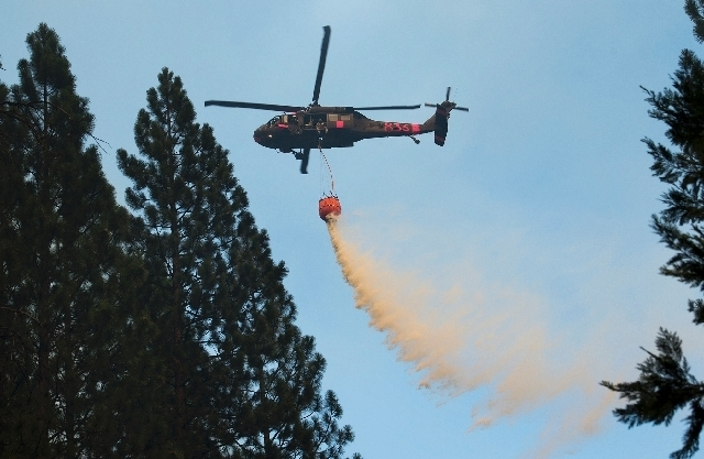 A helicopter makes an aerial water drop over the Rim Fire in the Stanislaus National Forest.