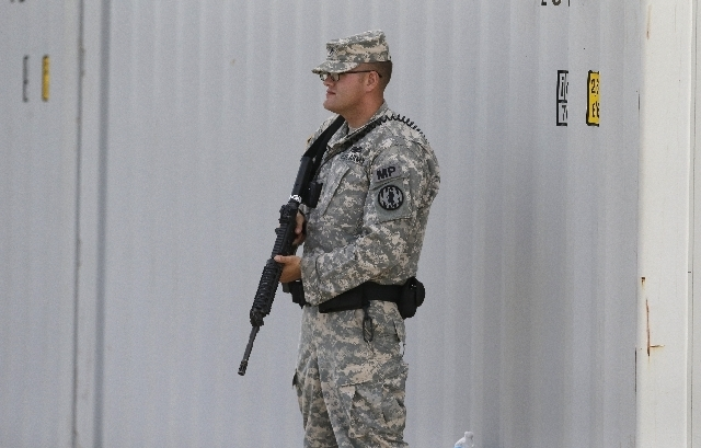 An armed soldier stands guard along a security barrier outside the courthouse holding the the court martial of Maj. Nidal Malik Hasan Friday, Aug. 23, 2013, in Fort Hood, Texas.  Military jurors a ...