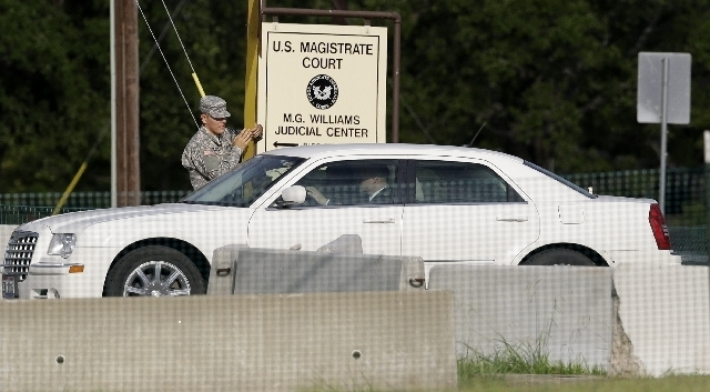 A guard raises the gate to for the stand-by defense lawyers heading to the court martial of Maj. Nidal Malik Hasan, Friday, Aug. 23, 2013, in Fort Hood, Texas. Military jurors are deliberating for ...