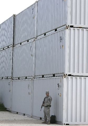 An armed soldier stands guard along a security barrier outside the courthouse holding the the court martial of  Maj. Nidal Malik Hasan Friday, Aug. 23, 2013, in Fort Hood, Texas.  Military jurors  ...