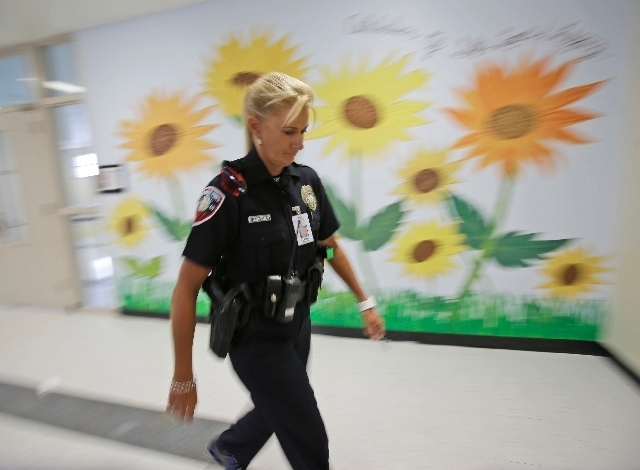 In this photo taken Thursday, Dara Van Antwerp, the school resource officer at Panther Run Elementary School Pembroke Pines, Fla. walks the hallways of the school where she teaches in the Gang Res ...