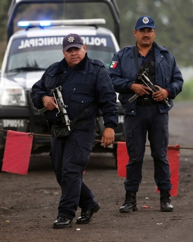 Municipal police guard the entrance to Rancho La Mesa where a mass grave was found in the municipality of Tlalmanalco, Mexico