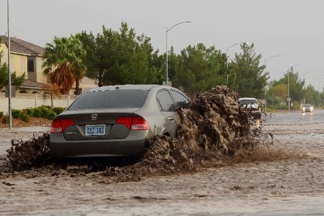 A car drives through flood waters at Grand Teton Drive and North Cimarron.