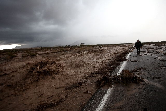 Violent flooding rages as a law enforcement officer works the scene on Kyle Canyon Road near Mount Charleston on Sunday
