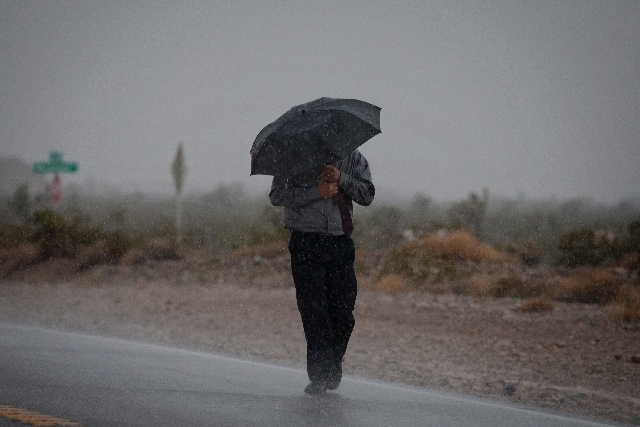 A man shields himself from pouring rain on Kyle Canyon Road near Mount Charleston on Sunday.