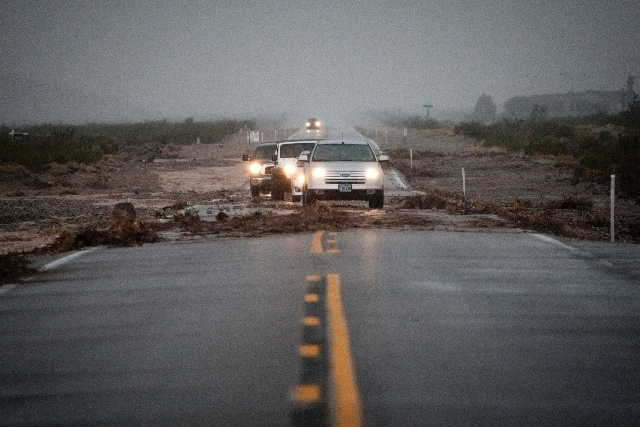 Cars pass debris on Kyle Canyon Road near Mount Charleston where it flooded on Sunday.
