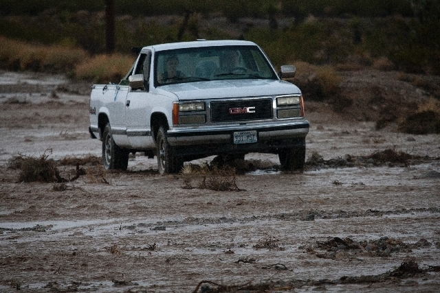 A truck passes through a flooded portion North Nicholson Street off Kyle Canyon Road near Mount Charleston on Sunday.
