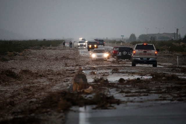 Cars pass through a flooded portion of Kyle Canyon Road near Mount Charleston on Sunday.