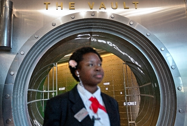"""In this Friday, Aug. 9, 2013 photo, Marilyn Buamah, a secret formula security officer, stands outside the vault containing the """"secret recipe"""" for Coca-Cola while waiting for a tour group at the ..."""
