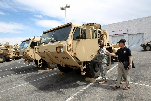 Sgt.1st Class Wallace Collier, left, and Nevada Army Reserve Ambassador Ashley Hall, a retired Army brigadier general, examine examine vehicles on Aug. 22 in a former Dodge dealership lot that the ...