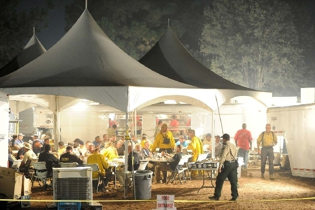 Firefighters chow under a series of tents set up at the Rim Fire incident command post 7 miles east of Groveland, after a long hard day of fighting the fire, which continues to conflagrate uncontr ...