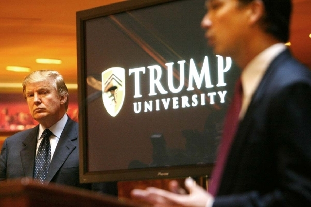 Donald Trump, left, listens as Michael Sexton introduces him at a news conference in New York on May 23, 2005, where he announced the establishment of Trump University. New York Attorney General E ...