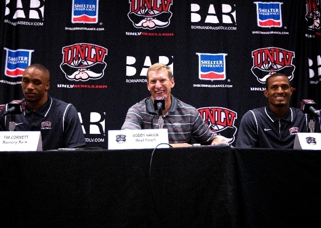 UNLV head football coach Bobby Hauck, center, speaks at a press conference at UNLV Monday, Aug. 26, 2013 in advance of Thursday's opener at Minnesota. At left is UNLV running back Tim Cornett and ...