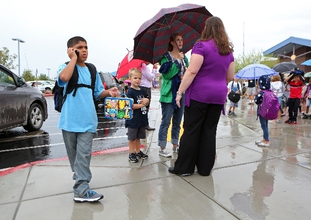 Daniel Perez, 9, left, speaks to his guardian about being picked up as school lets out at Bozarth Elementary on Monday. (Ronda Churchill/Las Vegas Review-Journal)