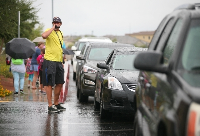 Erik Niemann, left, helps direct traffic as school lets out at Bozarth Elementary on Monday. (Ronda Churchill/Las Vegas Review-Journal)