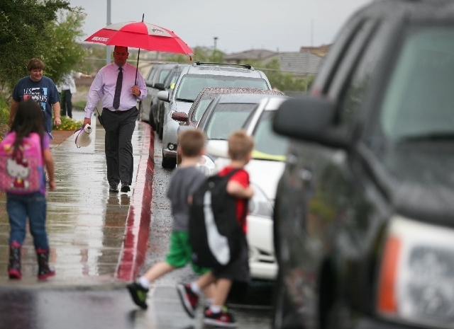 Principal Rodney Saunders, left, patrols the parking lot as school lets out at Bozarth Elementary on Monday. The principal is implementing a new system for parents to pick-up their students includ ...