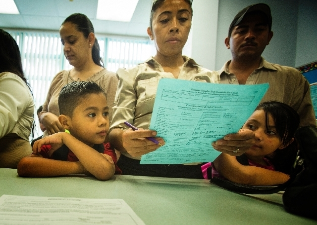 Fernando Alvarez, left, looks while his mother Lera registers for first grade at Cambeiro Elementary School at 2851 E. Harris Avenue during the first day of school on Monday. Cambeiro is one of 14 ...