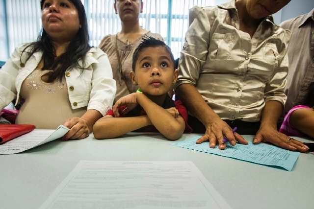 Fernando Alvarez, center, looks while his mother Lera, right, registers for first grade at Cambeiro Elementary School at 2851 E. Harris Avenue during the first day of school on Monday. Cambeiro is ...
