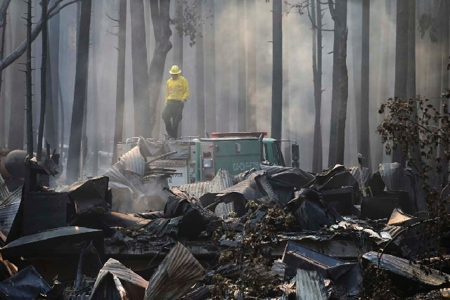 A firefighter stands on top of a fire truck at a campground destroyed by the Rim Fire near Yosemite National Park, Calif., on Monday, Aug. 26, 2013. Crews working to contain one of California's l ...