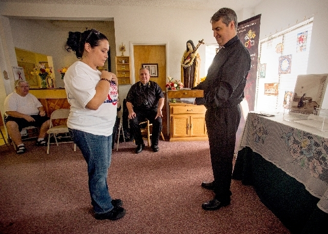 enny Montoya prays while the Rev. Andrew Small holds a writing desk that belonged to St. Therese of Lisieux at the St. Therese Center for HIV Outreach in Henderson. Small is taking the relics on a ...
