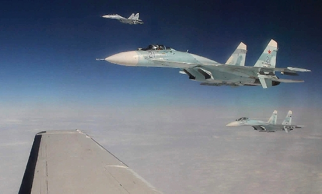 This photo made Tuesday, Aug. 27, 2013, over the Bering Strait near Alaska shows three Russian Federation Air Force SU-27s intercepting a passenger plane that was hijacked during a simulation to t ...