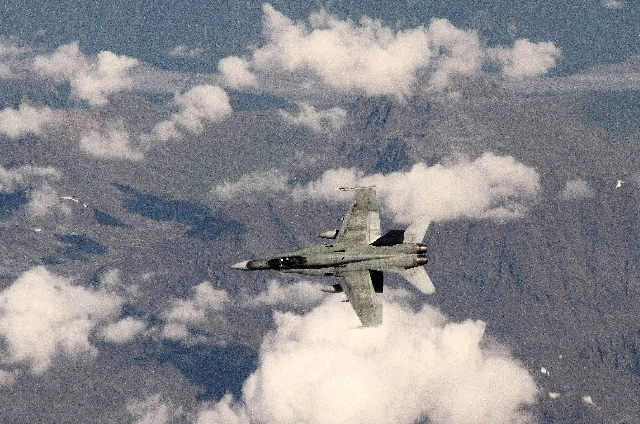 This photo made Tuesday, Aug. 27, 2013, shows a Canadian F-18 over western Alaska as it tracks a hijacked airplane in a simulation. The exercise by Canadian and U.S. forces from NORAD, along with  ...