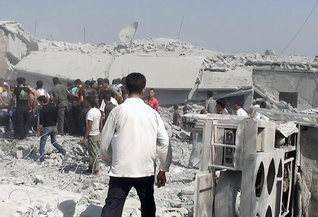 In this citizen journalism image provided by Edlib News Network, ENN, which has been authenticated based on its contents and other AP reporting, Syrians search under rubble to rescue people from h ...