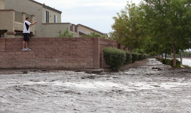 Tim Karas takes a picture of flooding on Grand Teton drive in the northwest part of the valley on Monday, August 26, 2013. (Justin Yurkanin/Las Vegas Review-Journal)