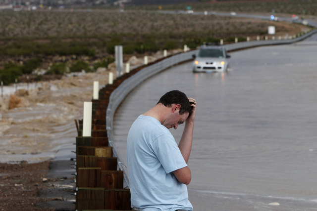 Ryan Mills waits for flood water to recede so he can get to his stalled vehicle, in background, on Volunteer Boulevard in Henderson, Nev. Saturday, Aug. 31, 2013. (John Locher/Las Vegas Review-Jou ...