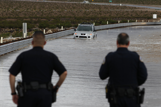 Henderson police officers watch as flood waters surround a stalled SUV on Volunteer Boulevard in Henderson, Nev. Saturday, Aug. 31, 2013. (John Locher/Las Vegas Review-Journal)