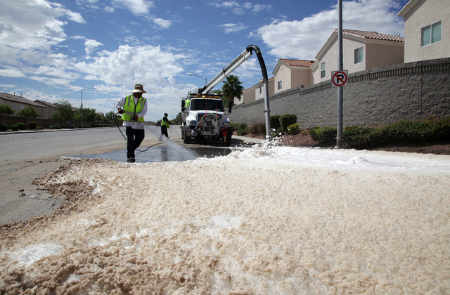 James Wheaton, a maintenance worker for the city of Las Vegas, sprays water to help a vactor truck suck up foam on El Capitan Way in the northwest Las Vegas on Tuesday, August 27, 2013. City and c ...
