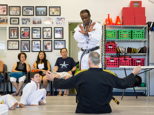 Master Daniel Jackson, standing, helps students test for their belts at the DoJang World Training Center in Henderson on Aug. 17. (Samantha Clemens/View)